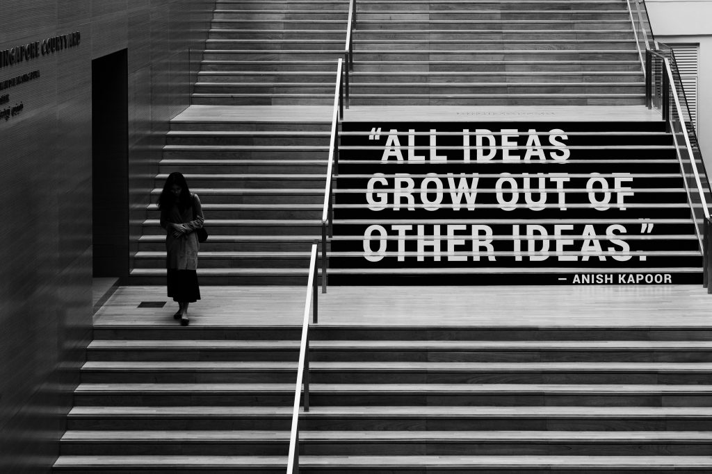 vrouw loopt over trap naar beneden. Tekst all ideas grow out of other ideas.