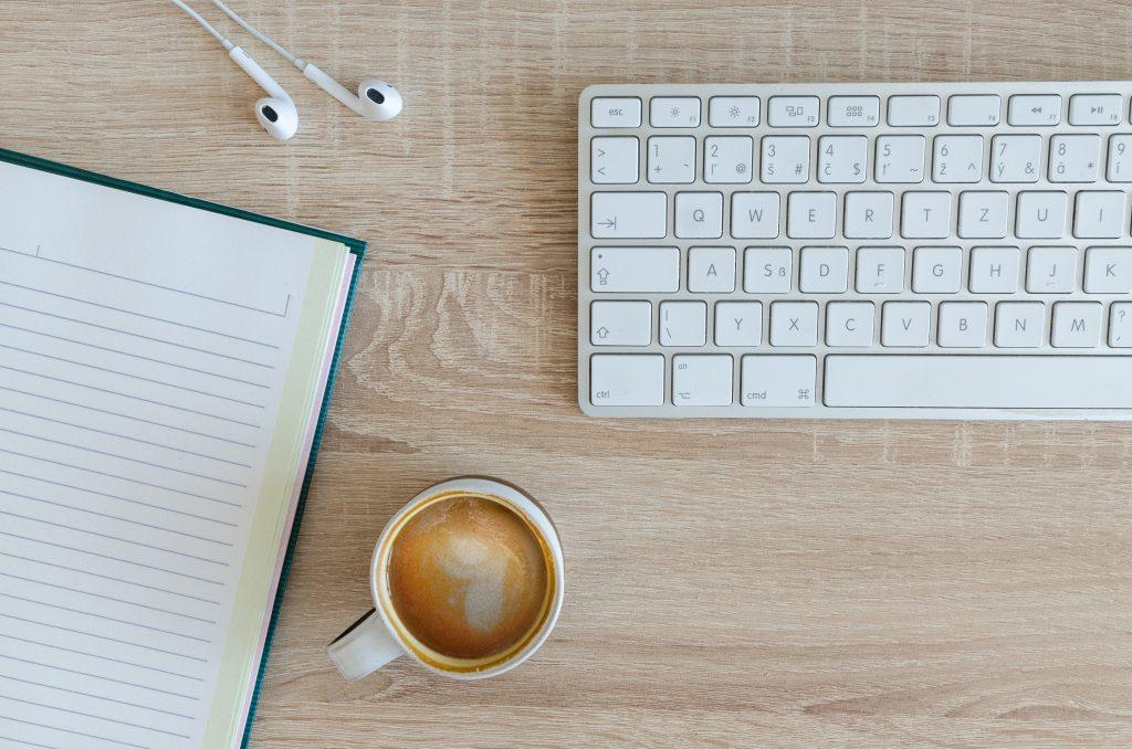 kop koffie met toetsenbord en notitieblok