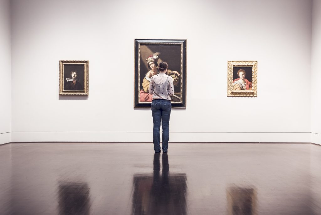 persoon kijkend naar schilderijen en kunst